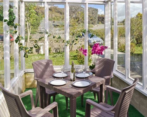 An interior view of an atrium dining area with garden views.