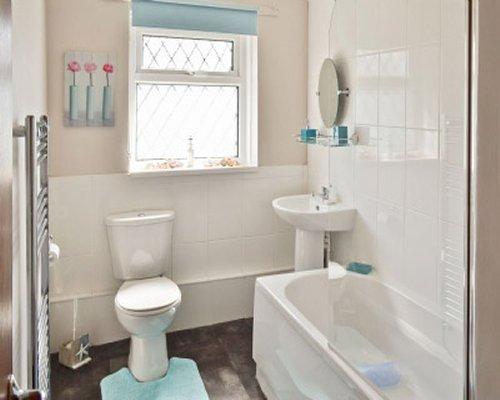 A bathroom with a bathtub and a window.