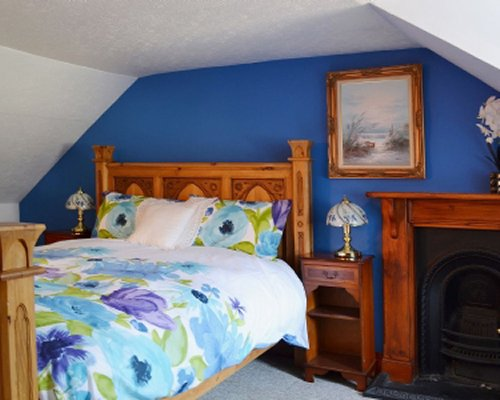 A well furnished bedroom with a fireplace.