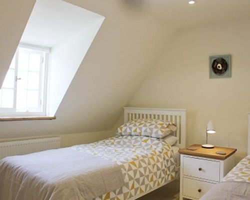 A bedroom with twin beds and a gabled window.