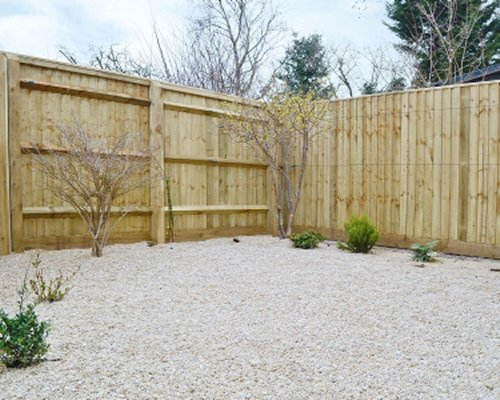 A view of stone filled backyard with the staggered fence.