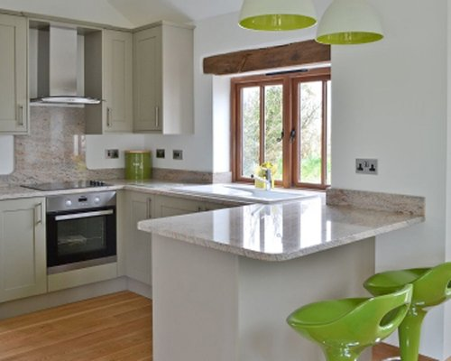 A well equipped kitchen with a breakfast bar and an outside view.