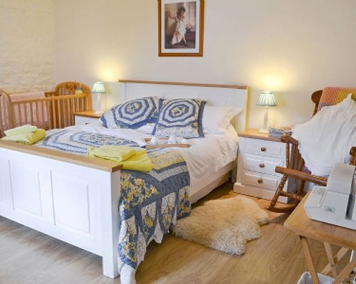 A well furnished bedroom with a wooden crib.