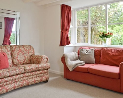 A well furnished living room with double pull out sofas and an outside view.