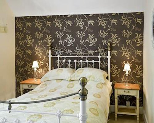 A bedroom with a large iron bed and nightstand lights.
