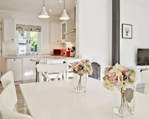 A well equipped kitchen with a window and dining table.
