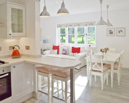 A well equipped kitchen with dining table and living area view.