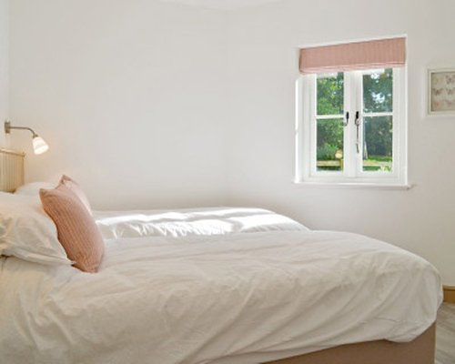 A bedroom with a large bed and a window.