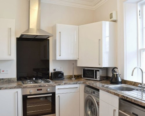 A well equipped kitchen with a stove and microwave oven.
