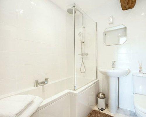 A bathroom with a bathtub shower sink and mirror.