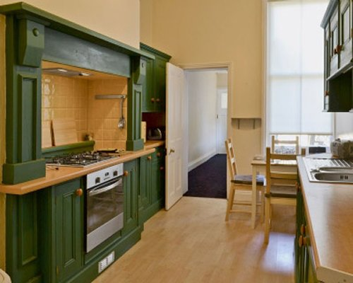 A well equipped kitchen with large stove and dining table.