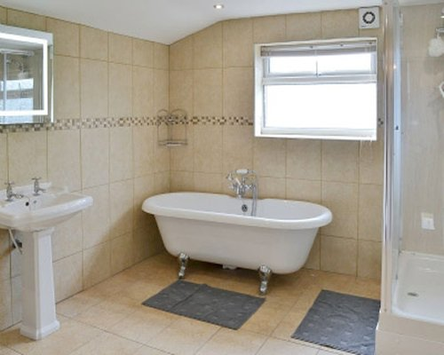 A bathroom with a pedestal sink and a claw foot bathtub.