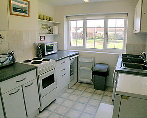 A well equipped kitchen with a microwave oven and outside view.