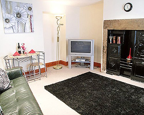 A well furnished living room with a television and dining area.