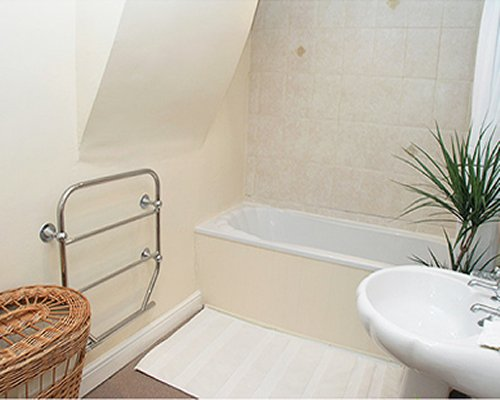 A bathroom with shower bathtub and a single sink.