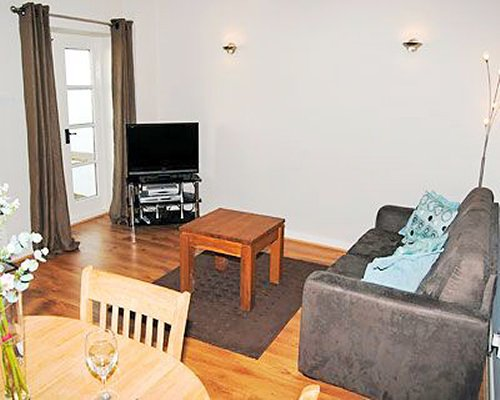 A well furnished living room with dining area and television.