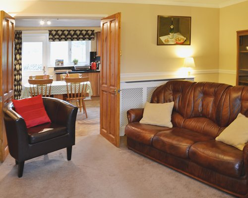 A well furnished living room with a view of the open plan kitchen with dining area.