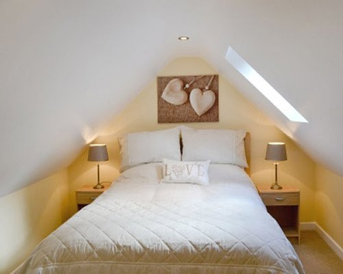 A bedroom with a large bed and a skylight.