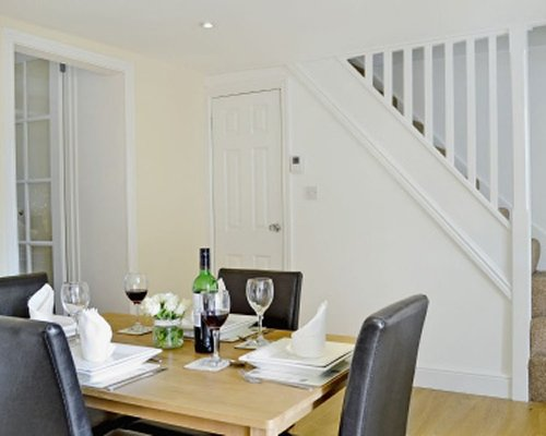 A well furnished dining room with a staircase.