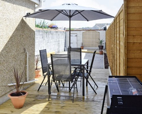 An exterior view of patio furniture with sunshades alongside a barbecue grill.