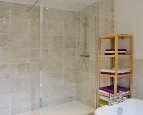 A bathroom with stand up shower and bathtub.