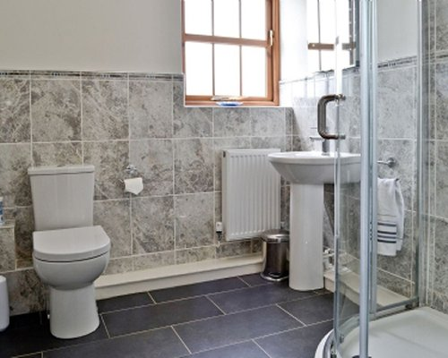 A bathroom with an open sink vanity toilet and shower stall.