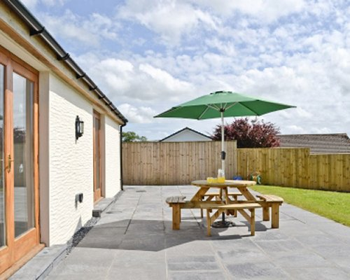 Outdoor dining with sunshade alongside a unit at Llanlliwe Cottage.