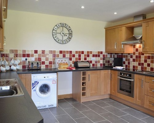A well equipped kitchen with a wall clock.