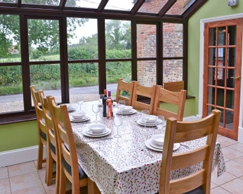 A glass roofed dining area with an outside view.