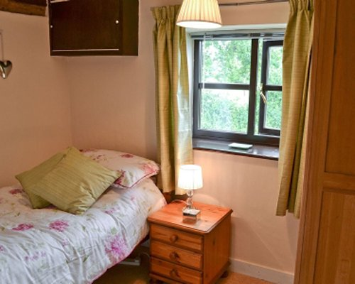 A well furnished bedroom with lamp and outside view.