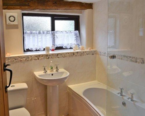 A bathroom with a sink toilet and bathtub.