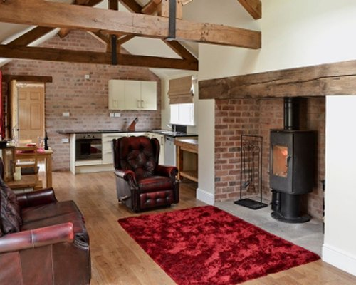 A well furnished living room with an open plan kitchen and a fire in the fireplace.