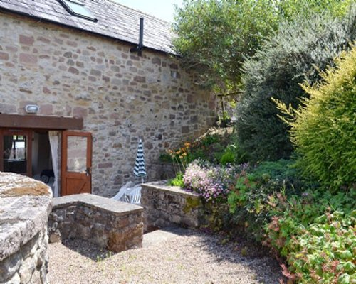 An exterior view of stone cottage entrance with patio and gardens.