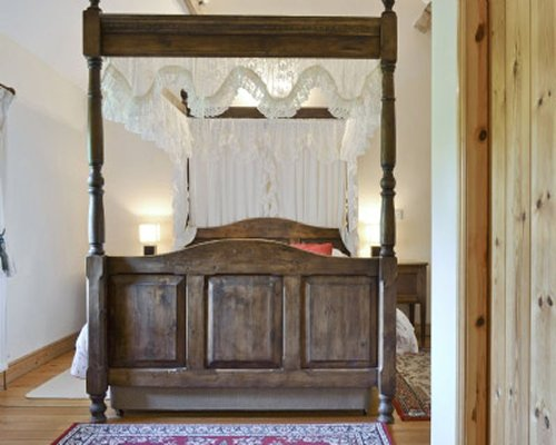 A bedroom with a large wooden canopy bed.