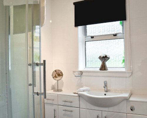 A bathroom with a sink vanity and shower stall.