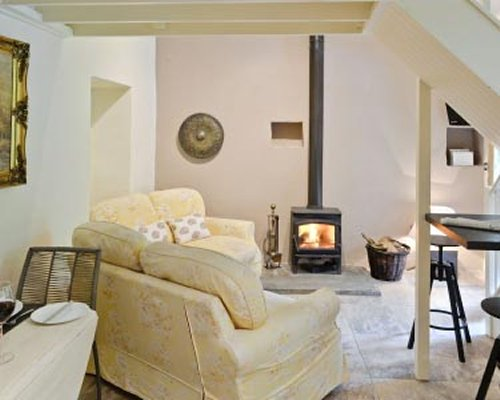 A well furnished living room with dining area and fire in the fireplace.