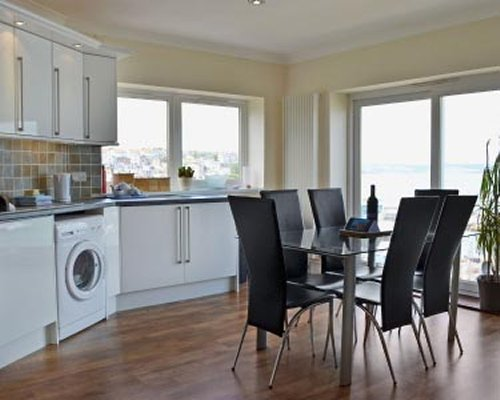 An open plan kitchen with dining area and outdoor view.
