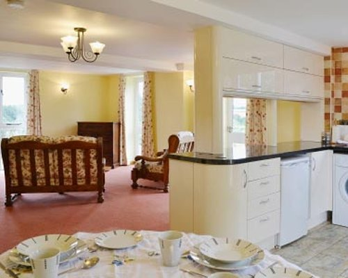 A well furnished living room and an open plan kitchen with dining area.