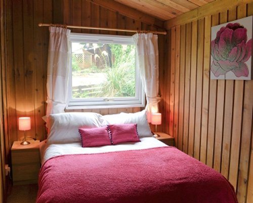 A well furnished wooden themed bedroom with an outside view.