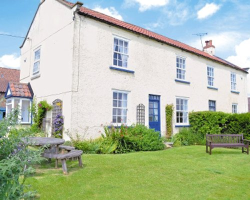Scenic exterior view of Foston Grange Cottage with an outdoor picnic.