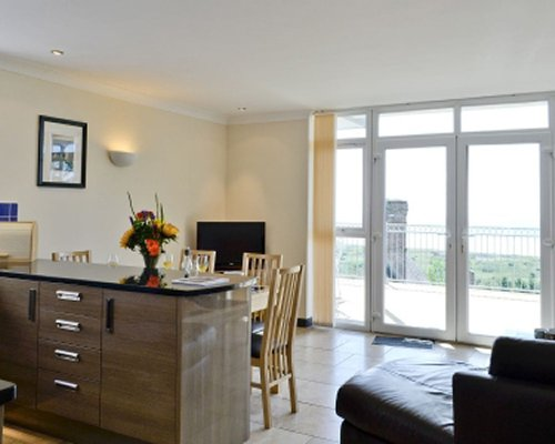 A well furnished living room with dining area television outside view and balcony.