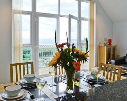 A well furnished dining room with a balcony.