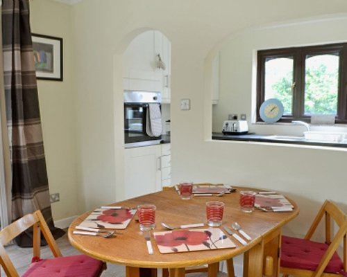 A well furnished dining area alongside kitchen.