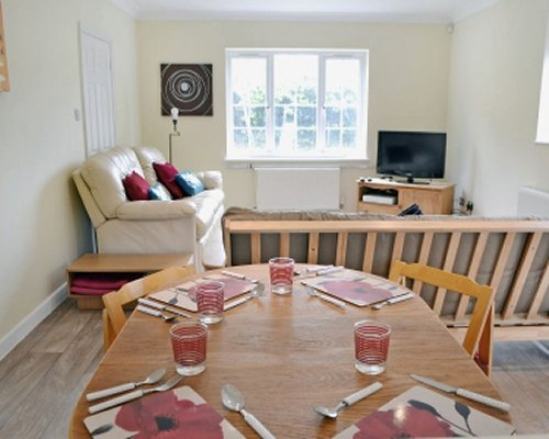 A well furnished living room with a television and wooden dining area.