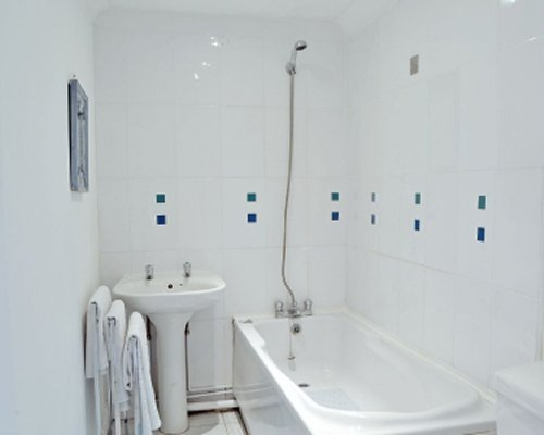 A bathroom with a shower bathtub and a single sink.