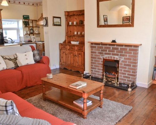A well furnished living room with a fireplace and an open plan kitchen.