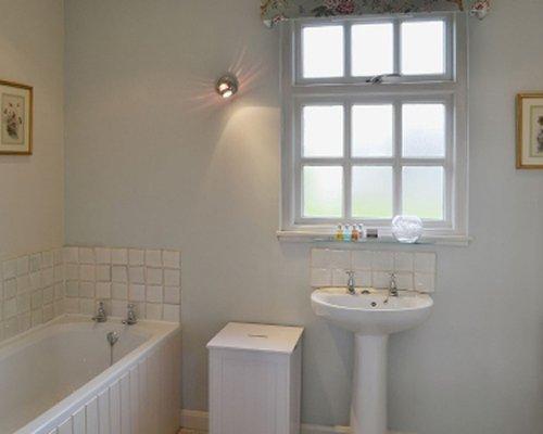 A bathroom with bathtub shower and sink.