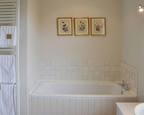 A white tile bathroom with bathtub.
