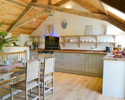 A well equipped kitchen with dining table and exposed wooden rafters.