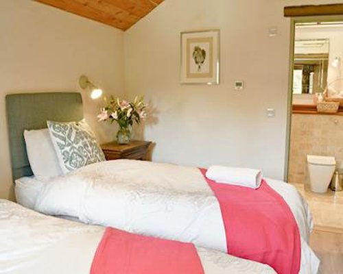 A well furnished bedroom with two twin beds alongside a bathroom.